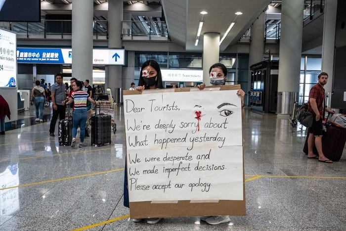On Wednesday, protesters at Hong Kong's airport offered travelers apologies, aware of the negative image they had presented in scuffles the day before. Credit Lam Yik Fei for The New York Times