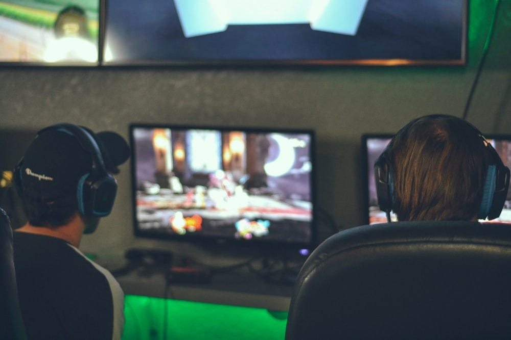 selective focus photography of two persons playing game in front of monitors