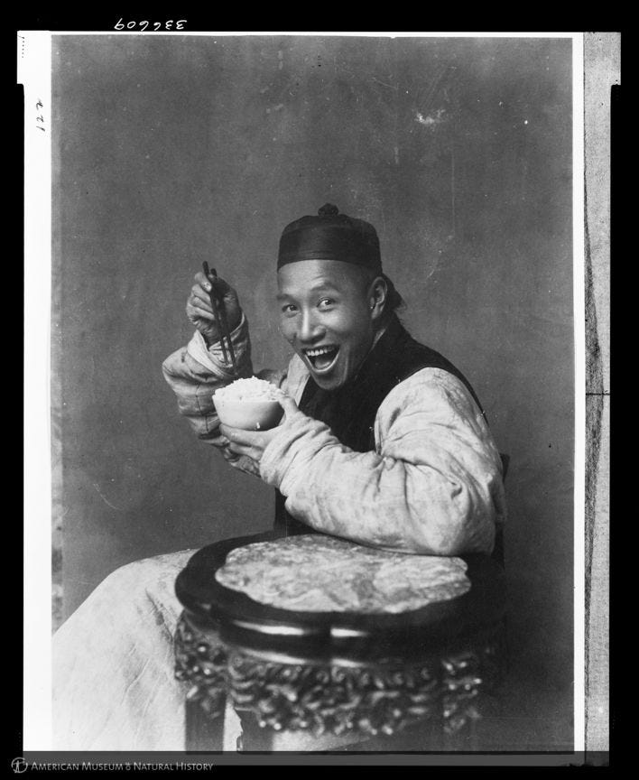 A picture from 1904 — yes, 1904 — of a man smiling while eating rice. (Laufer/AMNH)