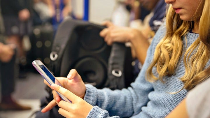 A teenager uses an iPhone while riding on public transit.