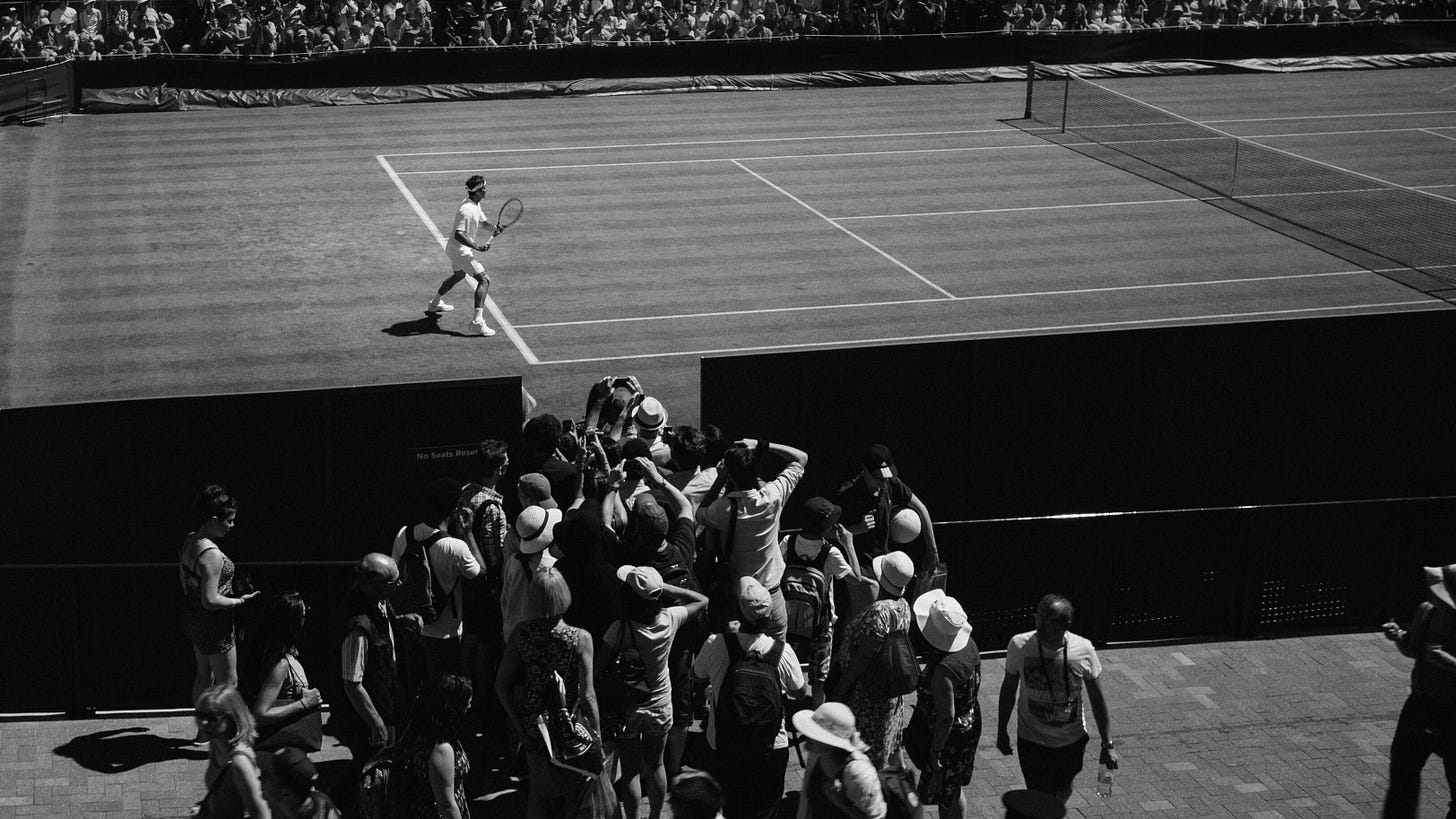 A group of spectators crowd on the sidelines to take photos of a tennis player.