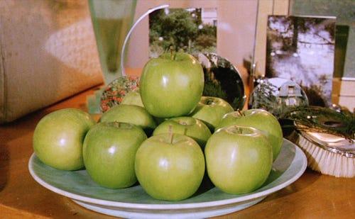 imagem de um prato cheio de maçãs verdes brilhantes