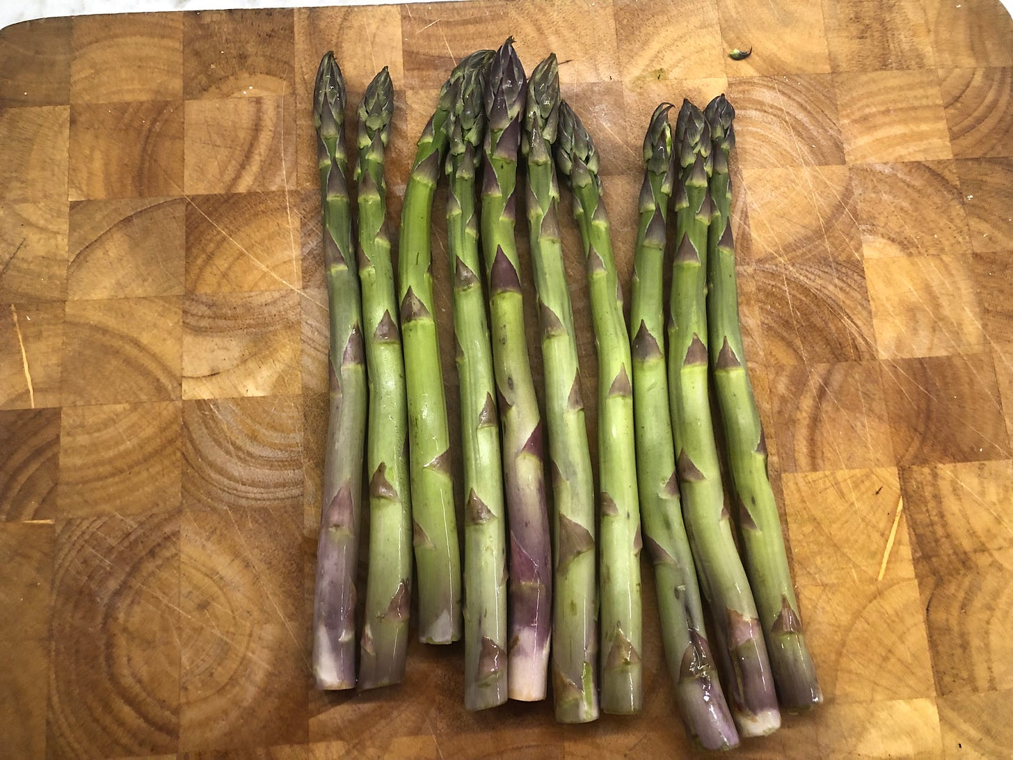 Ten spears of asparagus lying on a cutting board