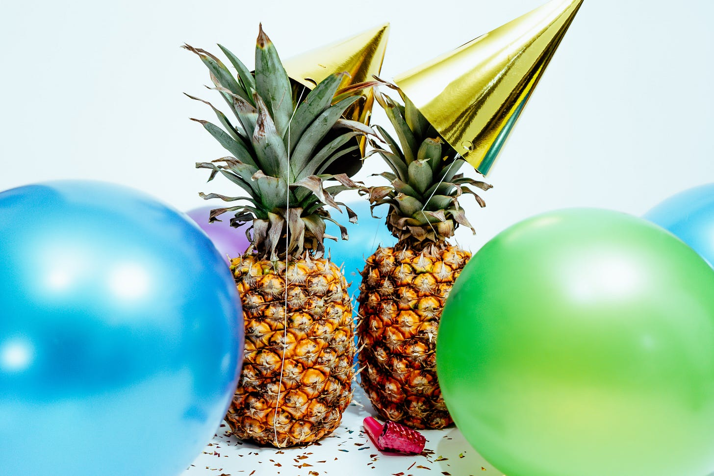 Pineapples with party heads and balloons