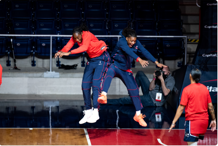 Tina Charles and Shavonte Zellous celebrate before the Washington Mystics May 21 game against the New York Liberty. Photo Credit: Domenic Allegra.