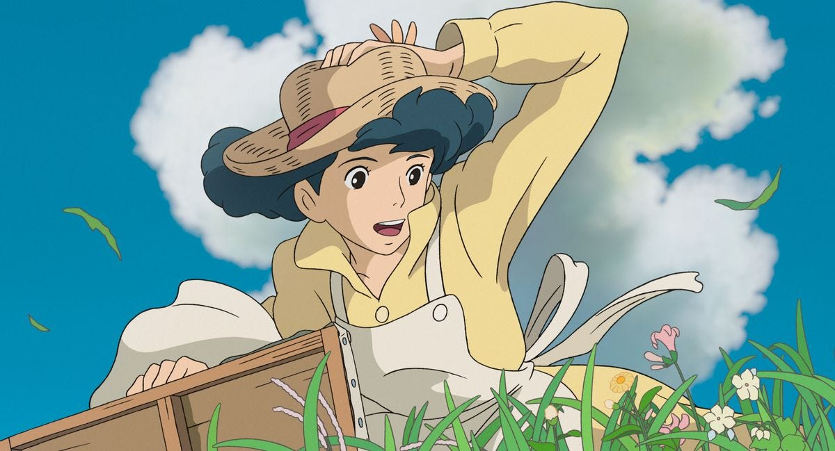 A woman in a green, flowery field clutches her hat against the wind in The Wind Rises