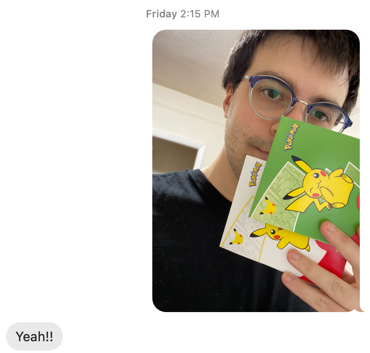"""Text conversation between author and his mother, where author sends photo of himself with two packs of Pokemon cards from McDonald's. Author's mother responds """"Yeah!!"""""""