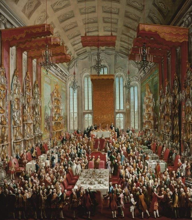 pintura a óleo reatratando um grande salão onde uma multidão se serve de mesas em um grande baquete colorido, as paredes repoletas de pratarias e o teto com vários lustres