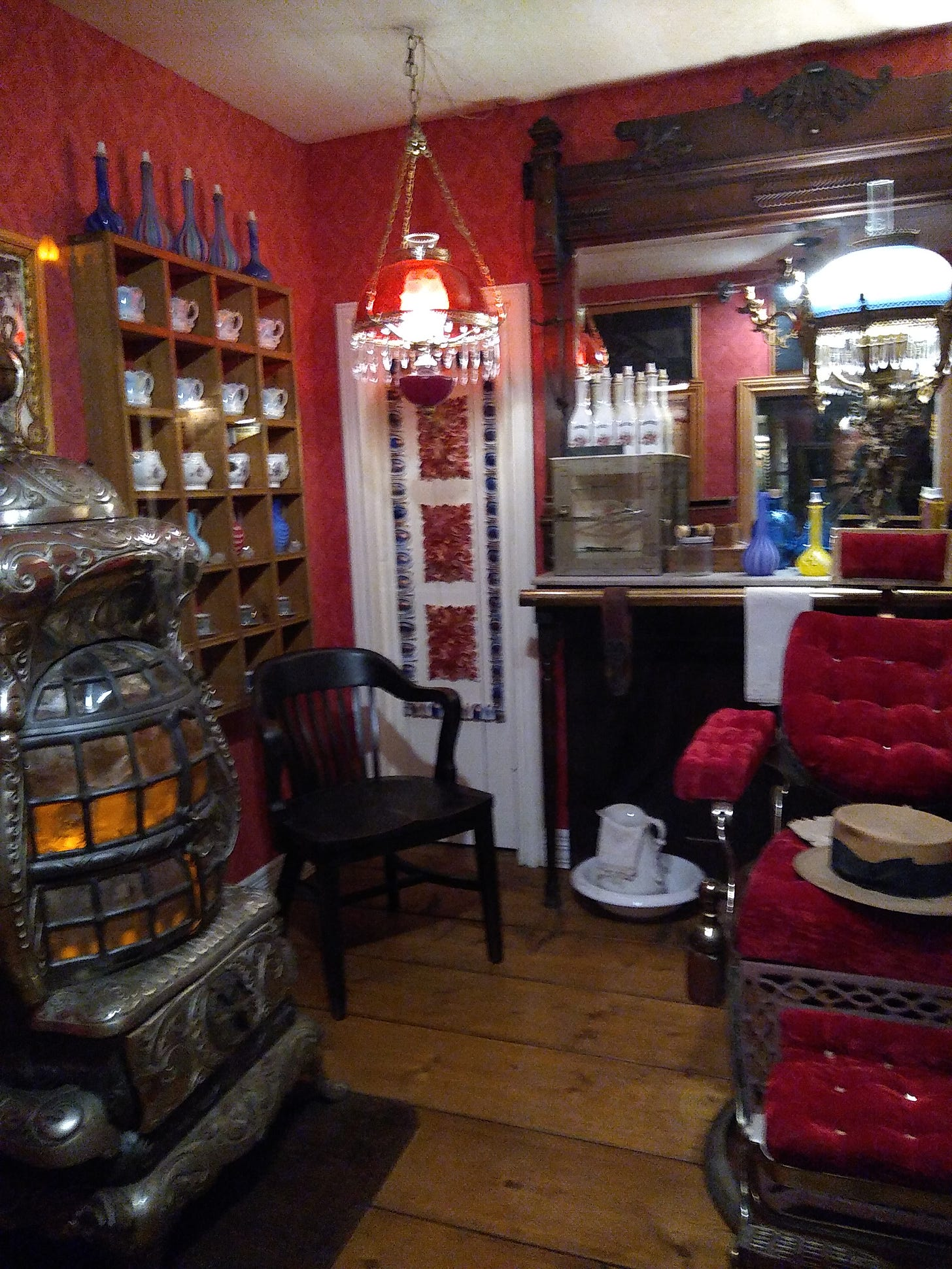 Victorian barbershop with chair, small bottles on shelves, and potbellied woodstove