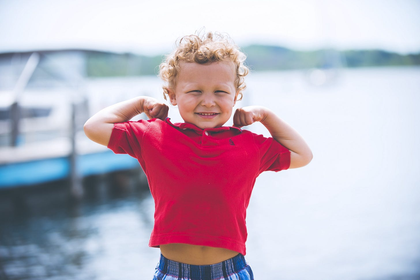 image of a strong small kid in a red t shirt for article by Larry G. Maguire