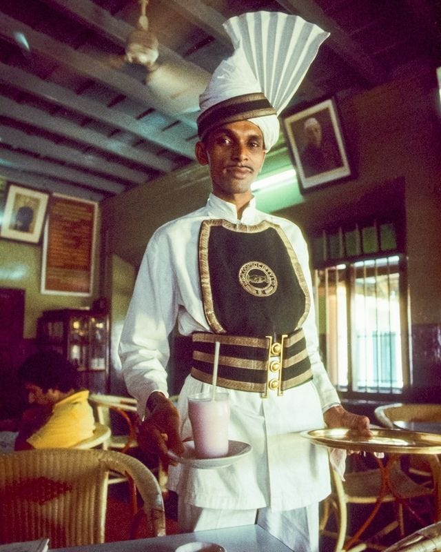 At a coffee house in Kerala, India, the traditionally garbed server brings a rose-water lassi, or yogurt drink. Overhead the fans try to keep things cool. - Kevin Kelly