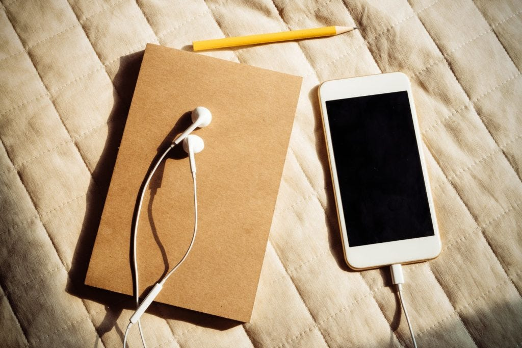 A light brown journal with a pencil above it and a white cellphone with white earbud headphones plugged into it lying next to the journal. These items are lying on the surface of a beige coverlet.
