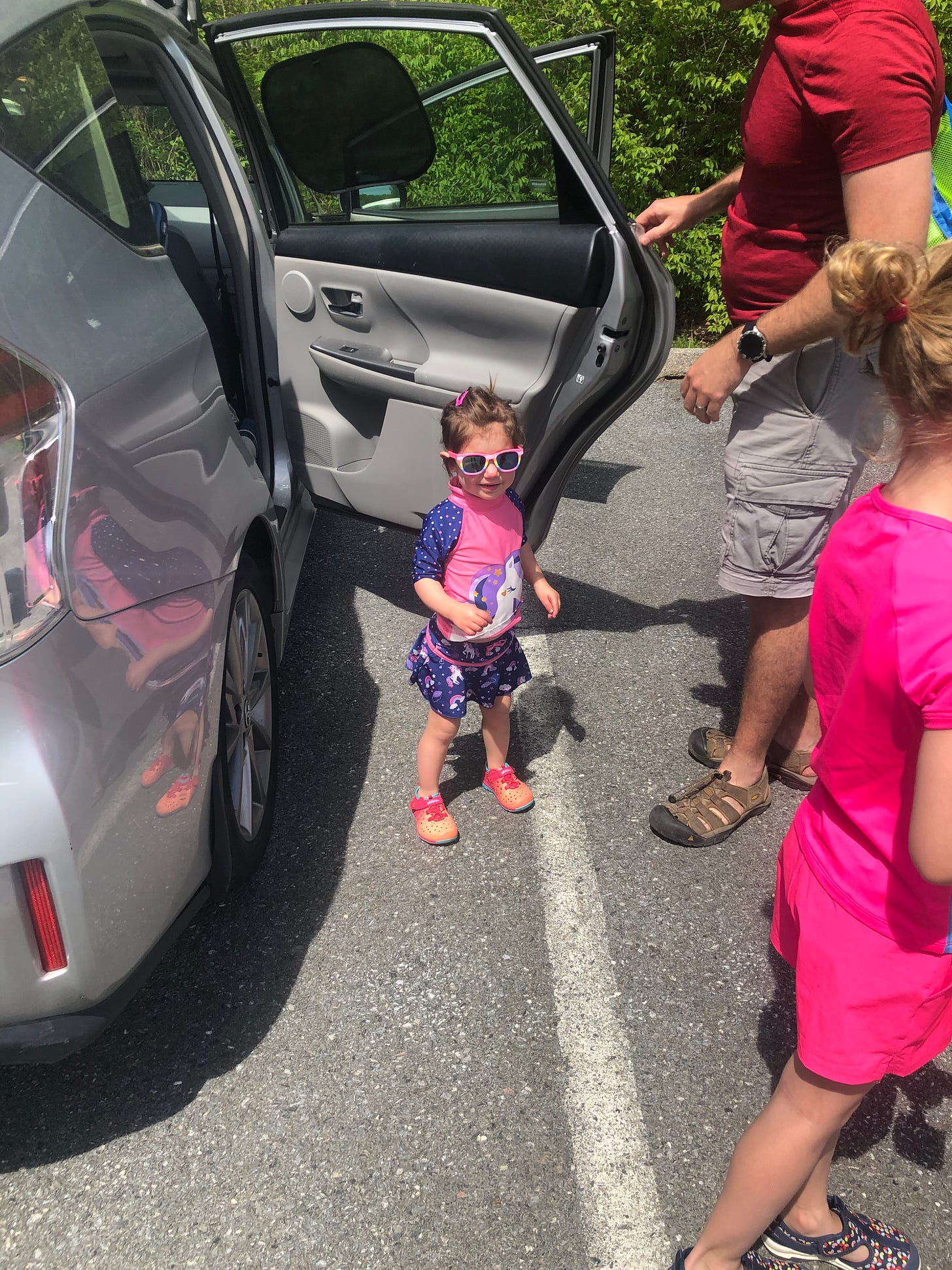 Photograph of Lila in swimsuit and sunglasses getting out of the car.
