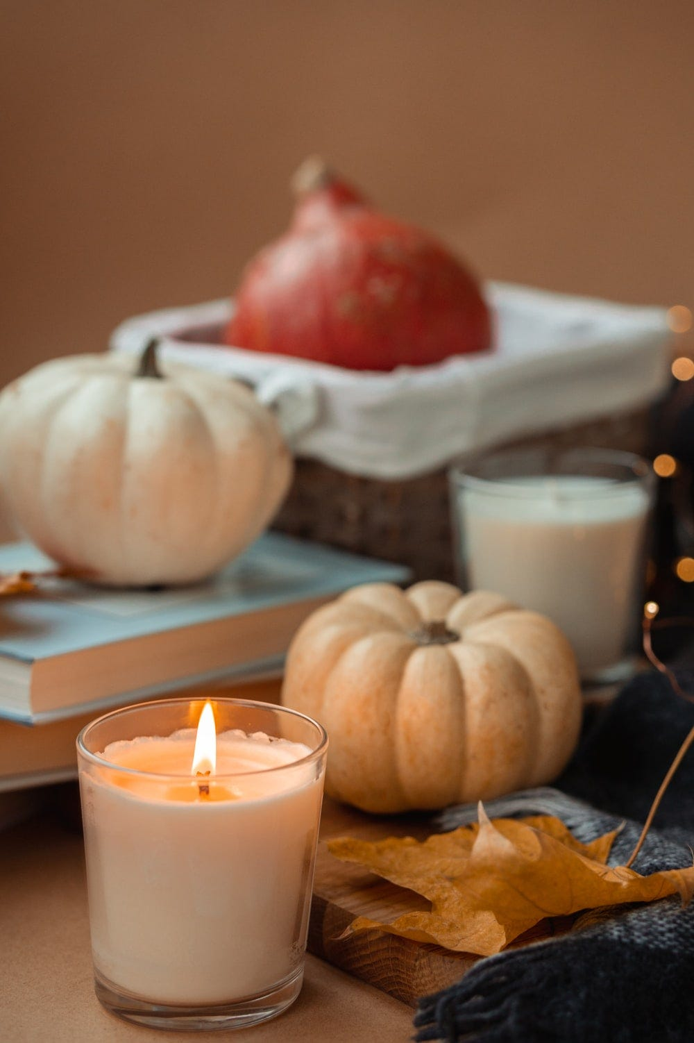 white and red round fruit beside white pillar candle on brown wooden table
