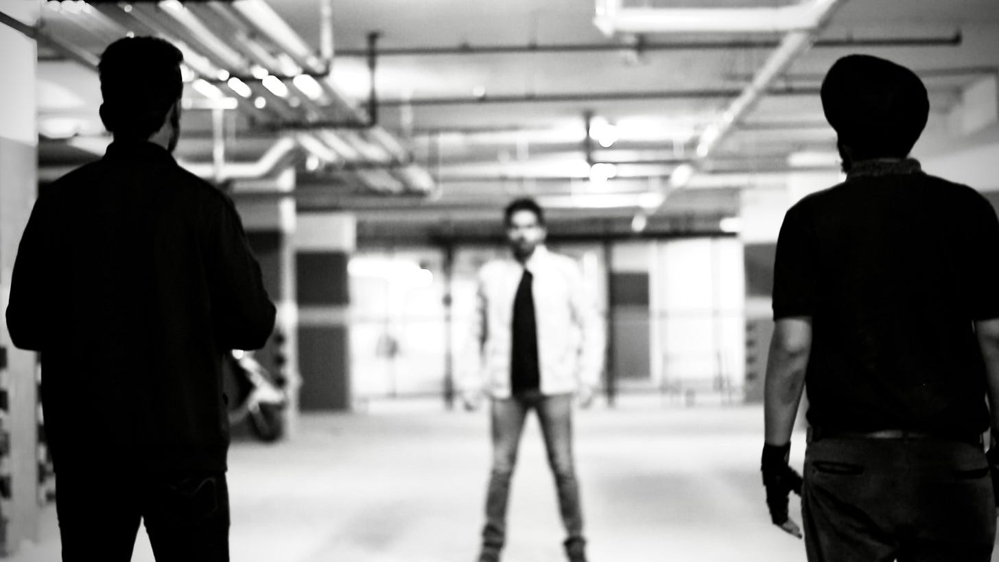 From 'The Glint of Darkness: Revolution': A man in a parking garage, slightly out of focus and facing the camera from far away, is confronted by two men in black shirts, in focus, backs to the camera.