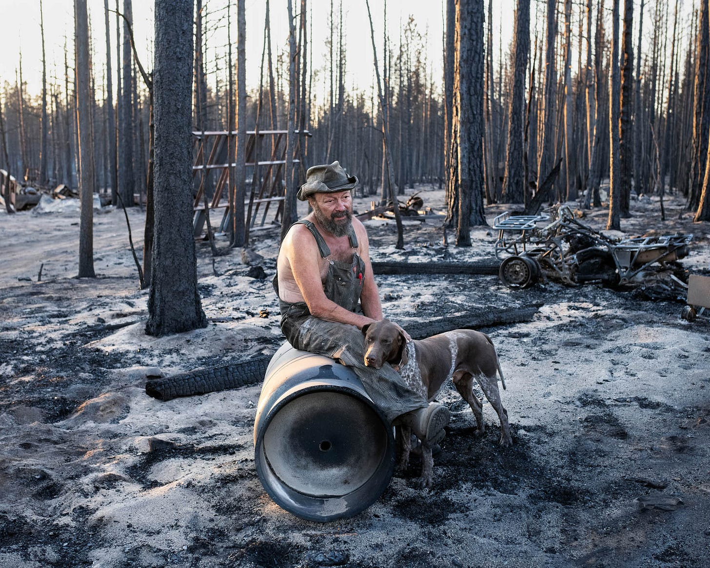 """Jeff Whited sits among his destroyed belongings on July 22. The Bootleg Fire arrived """"just like a freight train,"""" says Whited. """"It looks like a freaking bomb went off."""" The 63-year-old had been helping clean up the wreckage of his brother's burned-down house when flames reached his own. Guitars and amplifiers, snowmobiles and trucks, engine parts, chain saws, a huge cache of hand tools and much more—all gone, Whited says. """"This sure was a beautiful place,"""" he says. """"It doesn't leave a beautiful memory with me, not this picture of it."""" At the grave of his partner on his 12-acre property, wind chimes used to hang in the trees. Whited recalls asking why she wanted so many of them, to which she replied, """"When I'm gone, baby, you'll know I'm still there when you hear 'em."""" After the fire, he says, """"I can't hear one. They're gone. Every wind chime."""""""