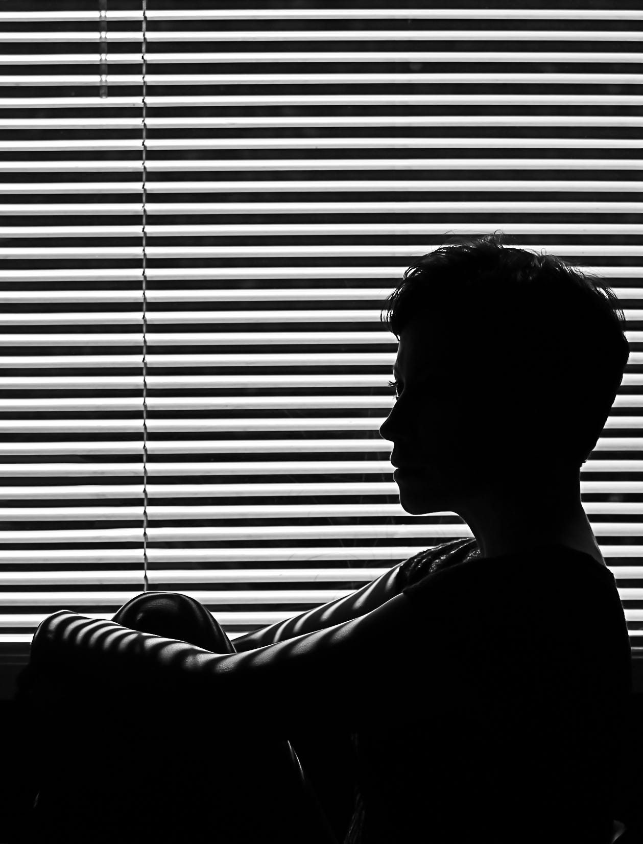 Someone siting alone in a dark room