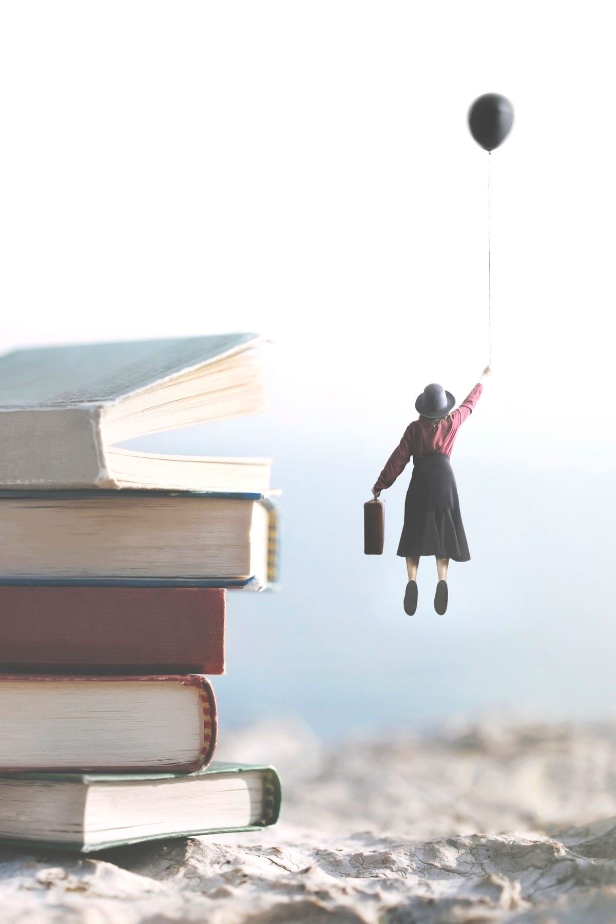 Woman Holding Balloon Floating Beside Giant Stack of Books on Beach