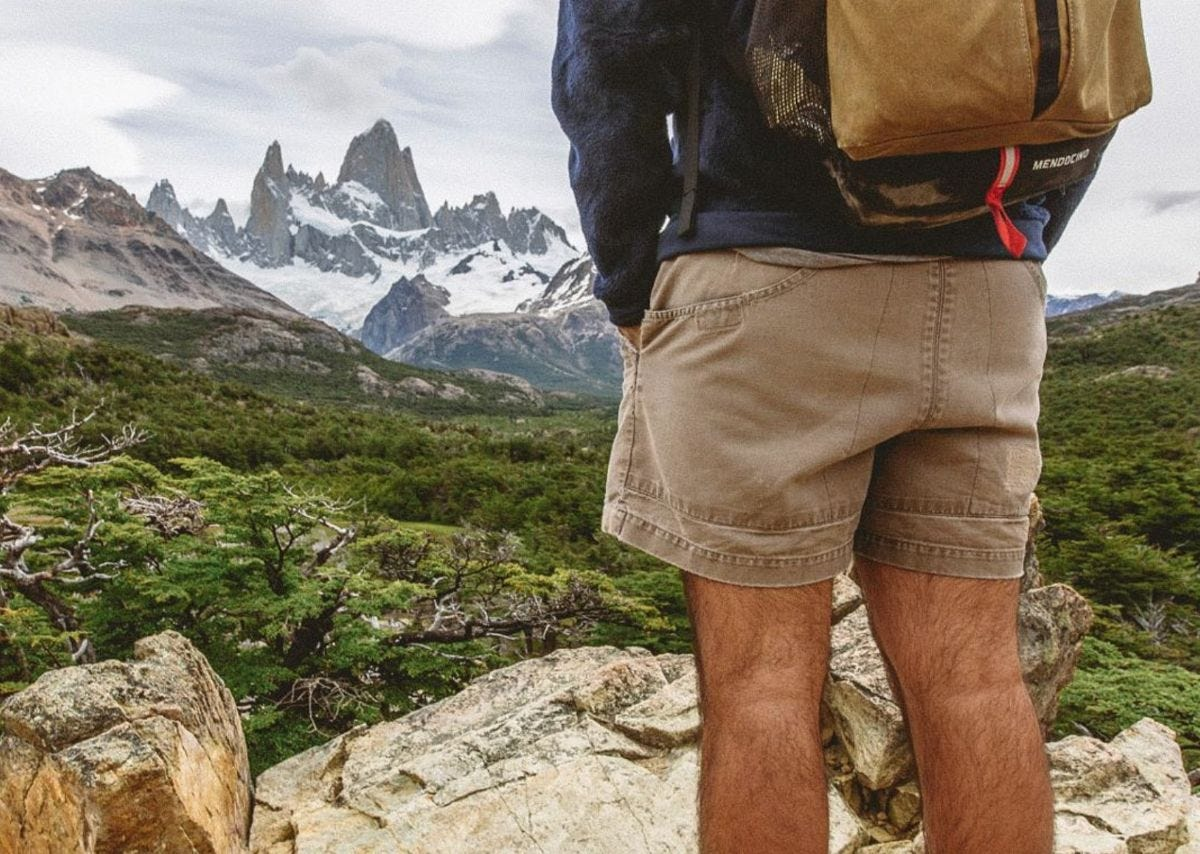 a man wearing patagonia stand up shorts stands in front of mount fitz roy in patagonia south america