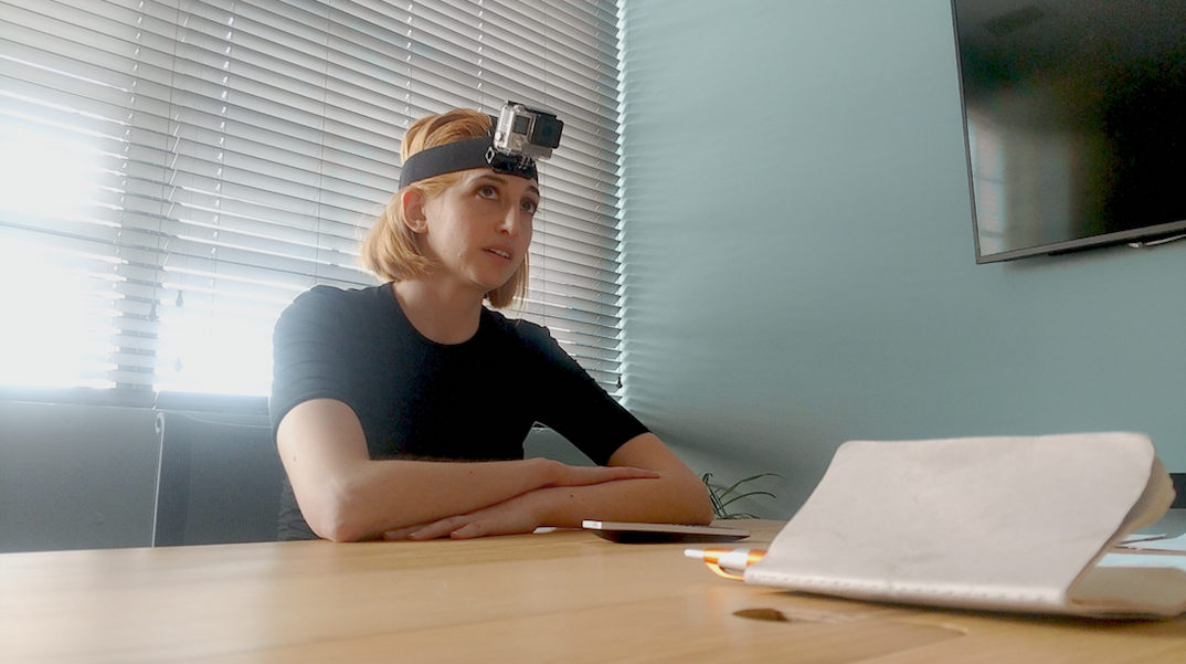 From the film 'I Blame Society': A blonde woman sits at a desk, wearing a Go-Pro camera on her forehead, looking at unseen characters in the room.