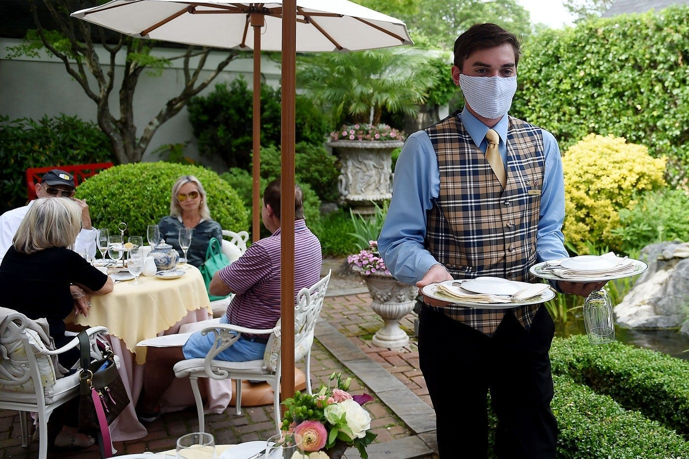 A masked waiter serves a group at an upscale restaurant in Virginia, days into its reopening amid the pandemic.