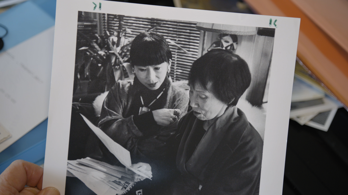 A photo of Amy Tan and her mother looking at a piece of paper. The photo is in black and white and has a thick white border with minor markups. You can see part of a hand holidng it, with a smattering of documents and photos in the background.