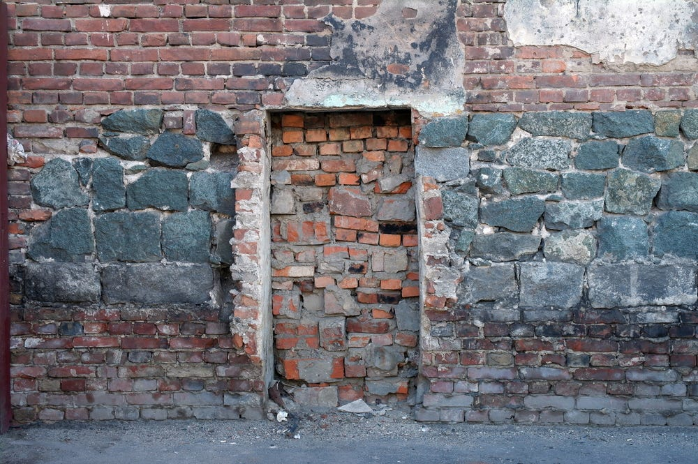 old wall of stone and red brick with a bricked up door