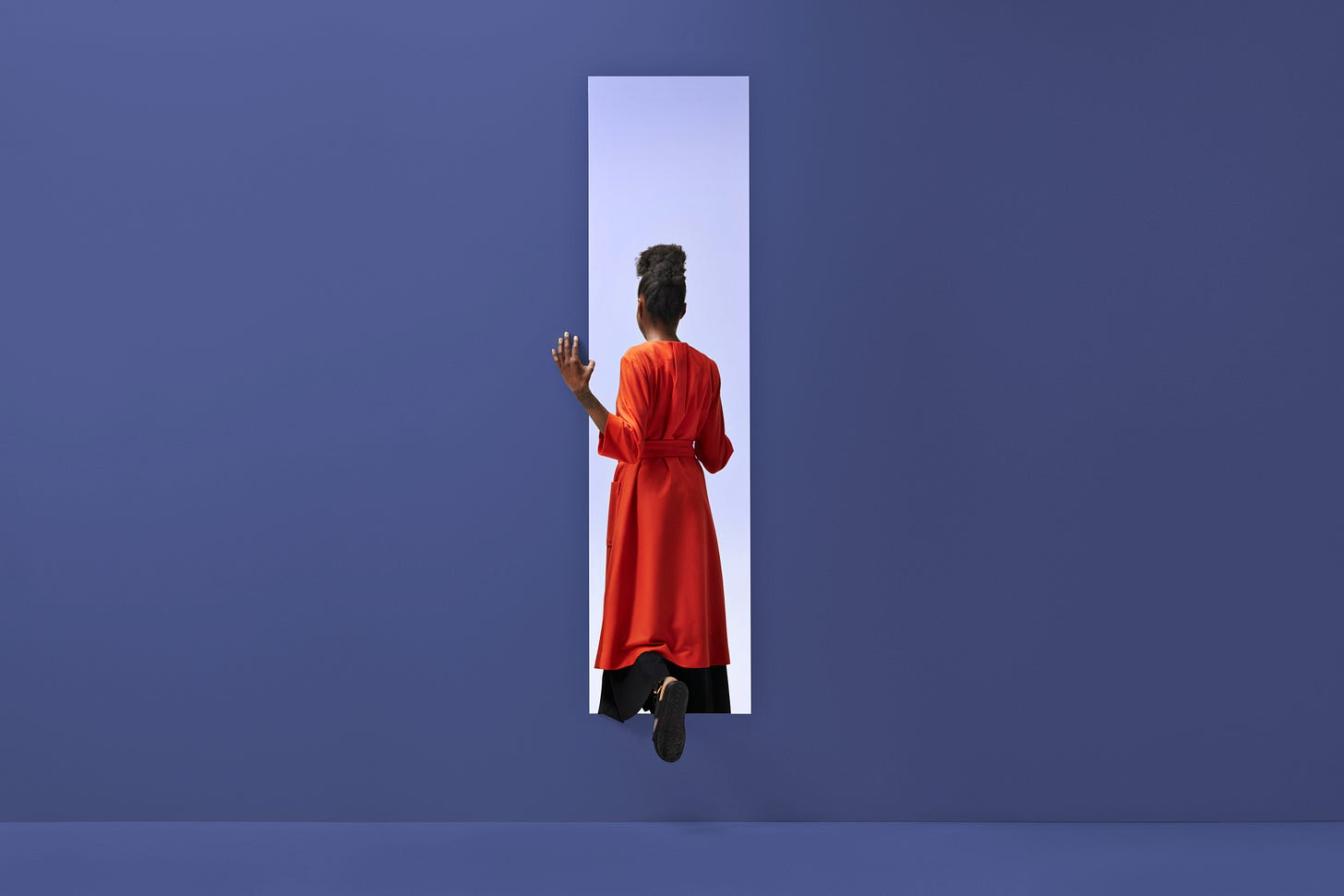Image of a Black woman standing with her back to us, in a dreamlike purple doorway, poised as though she might go through