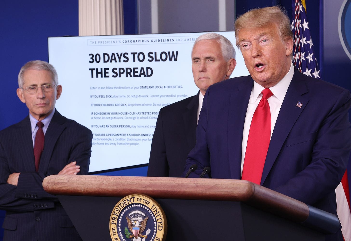 """Dr. Anthony Fauci, Mike Pence, and Donald Trump stand in front of a graphic titled """"30 DAYS TO SLOW THE SPREAD"""" on March 31, 2020"""
