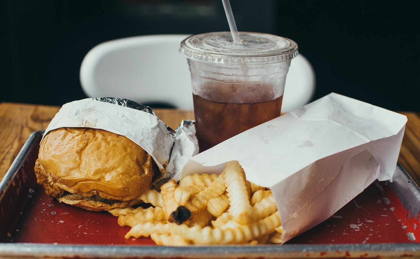 image of a burger, fries and fizzy drink on a tary for article by Larry G. Maguire on fitness
