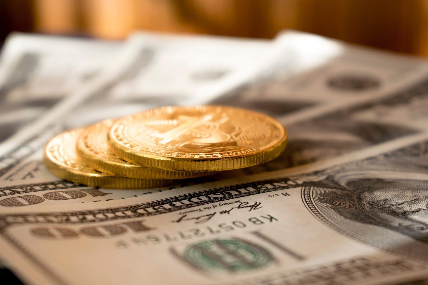 Three gold Bitcoins on four USD$100 bills.