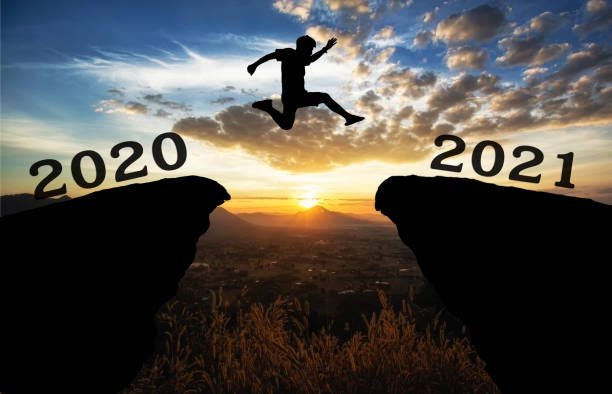 A young man jump between 2020 and 2021 years over the sun and through on the gap of hill  silhouette evening colorful sky. A young man jump between 2020 and 2021 years over the sun and through on the gap of hill  silhouette evening colorful sky. happy new year 2021. 2021 stock pictures, royalty-free photos & images