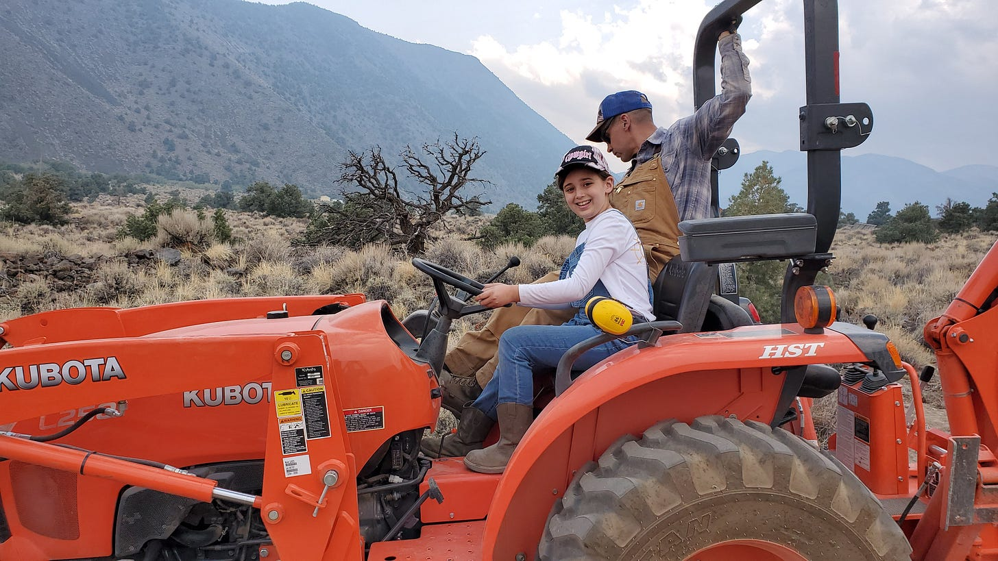 C and Eric on a Kubota tractor. C is smiling at the camera while Eric looks down to the right.