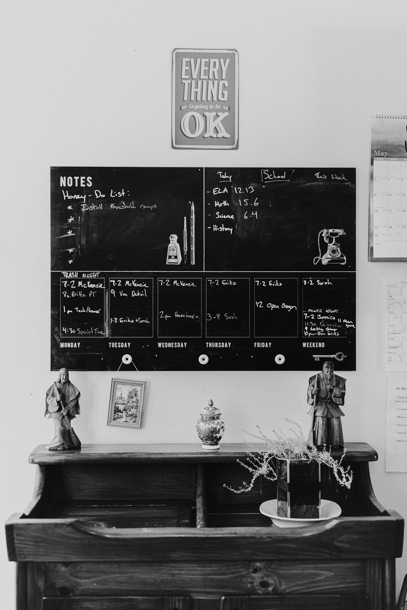 """A sign stating """"Everything is going to be OK"""" hangs above a messy chalkboard calendar with numerous details written in and a wooden dry sink with knickknacks on it."""