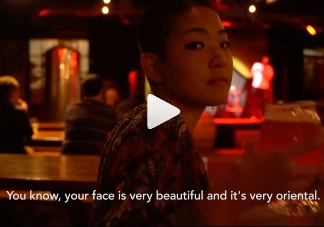 """Kyoko Takenaka is pictured, staring at the camera in a bar, with subtitles on the screen that read """"you know, your face is very beautiful and it's very oriental."""" A play button is overlaid on top of the image."""