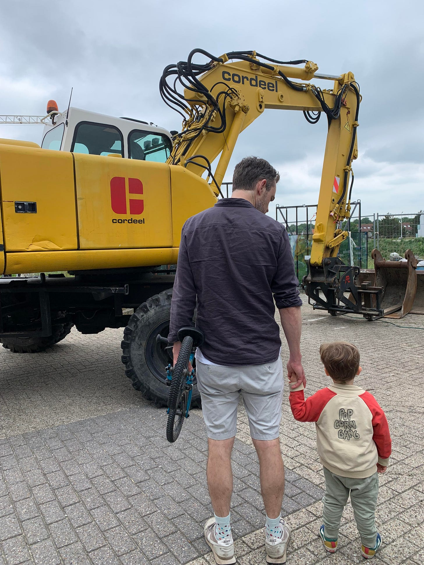 A photo of a boy and his son looking at a large yellow digger.