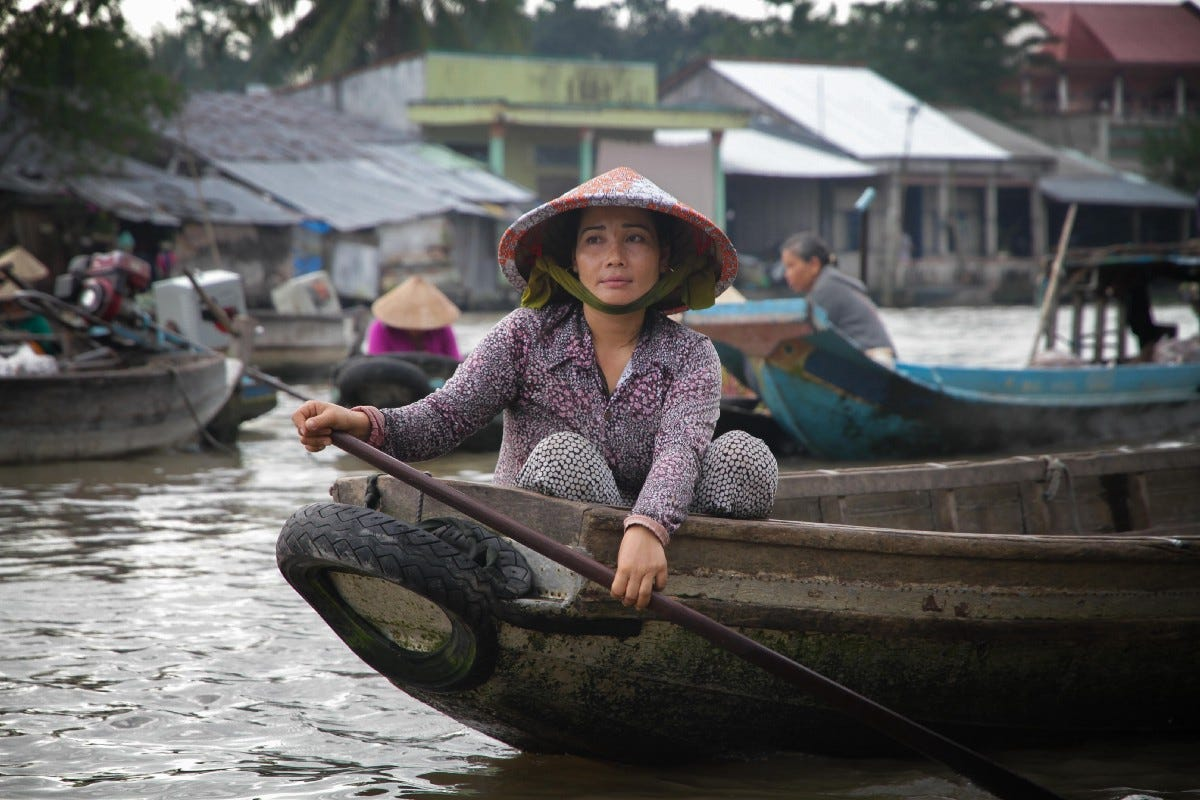 woman paddling on boat in Can Tho, Vietnam