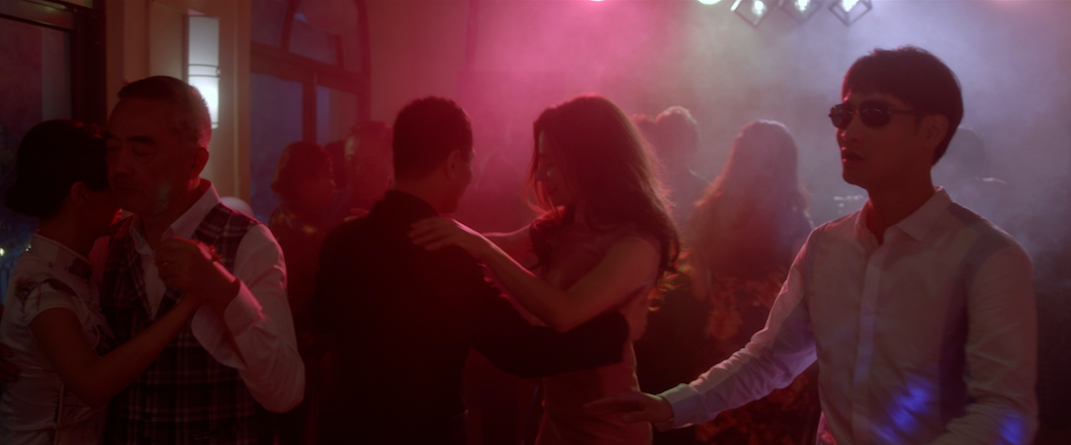 """From the film """"Touch"""": At a dance party, colored lights cover a group of tango couples, as a blind man tries to walk through."""