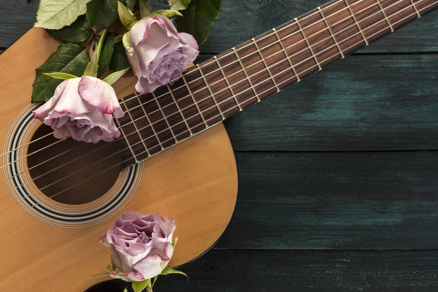 Image of a guitar on a wooden floor with pink roses