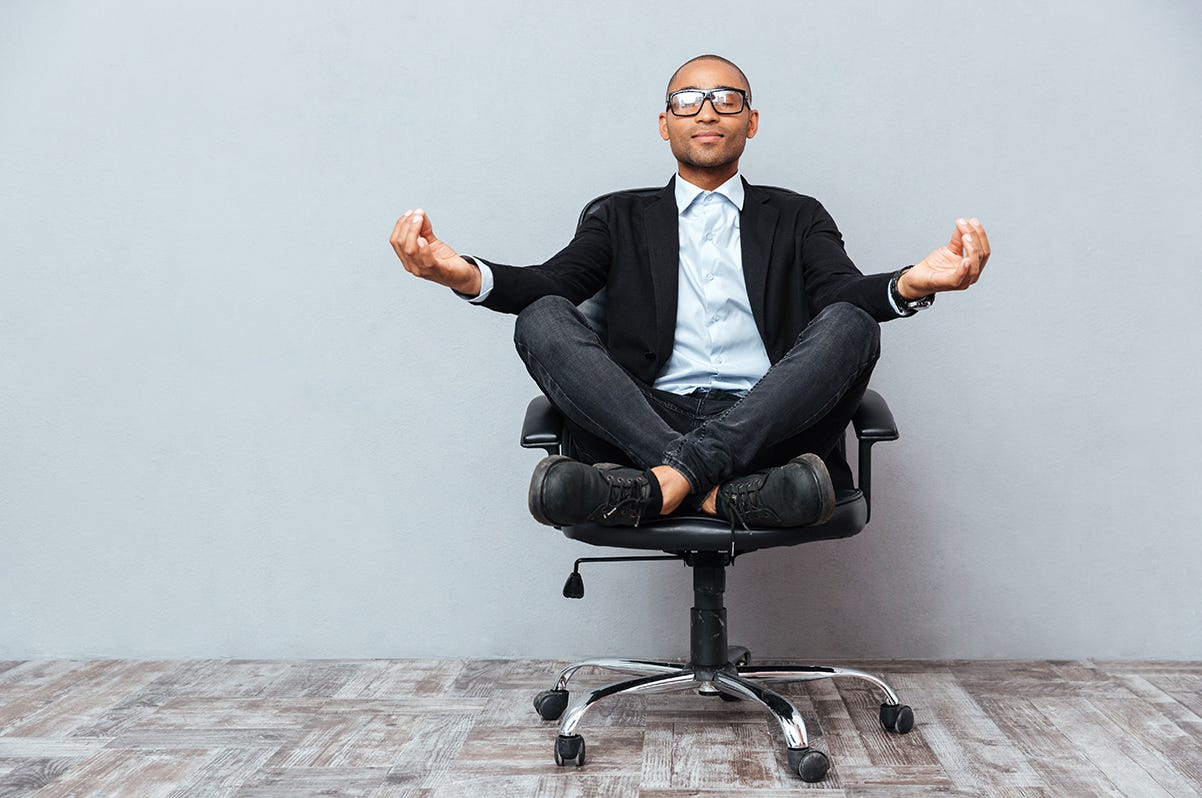 A person in a suit sitting on a chair  Description automatically generated with low confidence