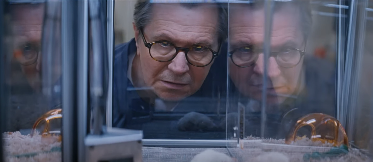 """From the film """"Crisis"""": Gary Oldman, playing a scientist with glasses, stares concerned into a glass cage with experimented on mice."""