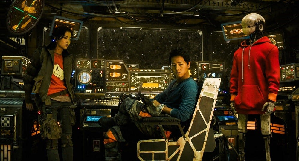 Three characters (from left to right: a woman, a man, and a robot) in a still from SPACE SWEEPERS, sitting at the cockpit of their space ship in staring at each other.