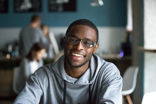 Portrait of smiling African American student looking at camera sitting in cafe