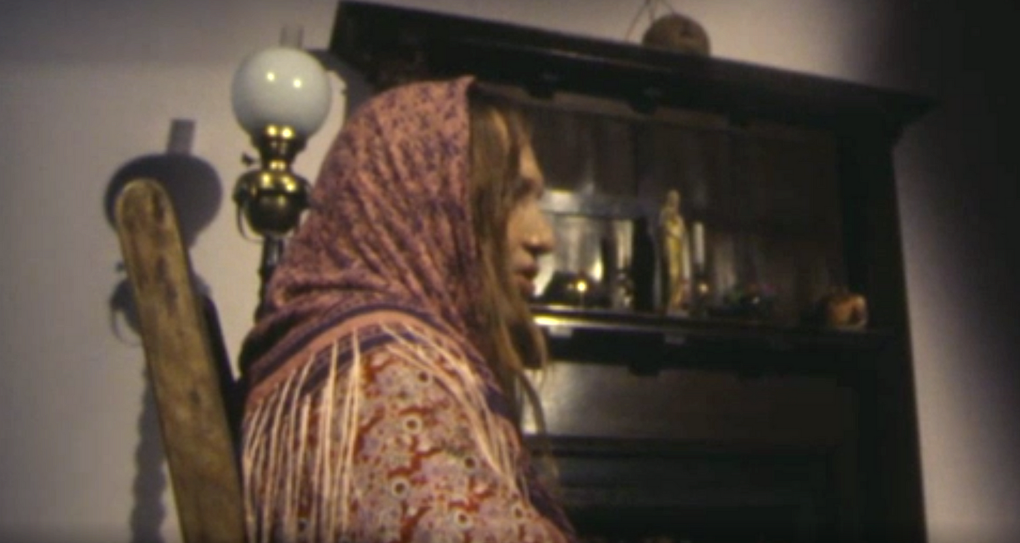 Still from an Irish television program showing a woman in traditional garb viewed from the side so her full face is not visible.