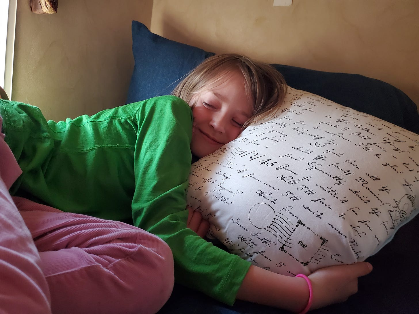 L smiling with her eyes closed and her head pressed against a white pillow in the top bunk.