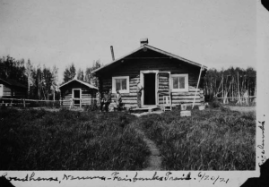 "Photo caption: ""Sizeland's Roadhouse, Nenana - Fairbanks [Trail? Train?], 6/20/21 [6/20/22]"" Surrounding photographs in this collection are dated in year, 1922, so 1921 may be incorrect. This photo shows a man standing with his hands on his hips by the doorway of a cabin facing two other men sitting down. There's a chair to the right of the doorway. Two smaller cabins are located to the left. A dirt path leading up to the larger cabin has been worn away through a dense patch of brush. [UAF-1969-89-108]"