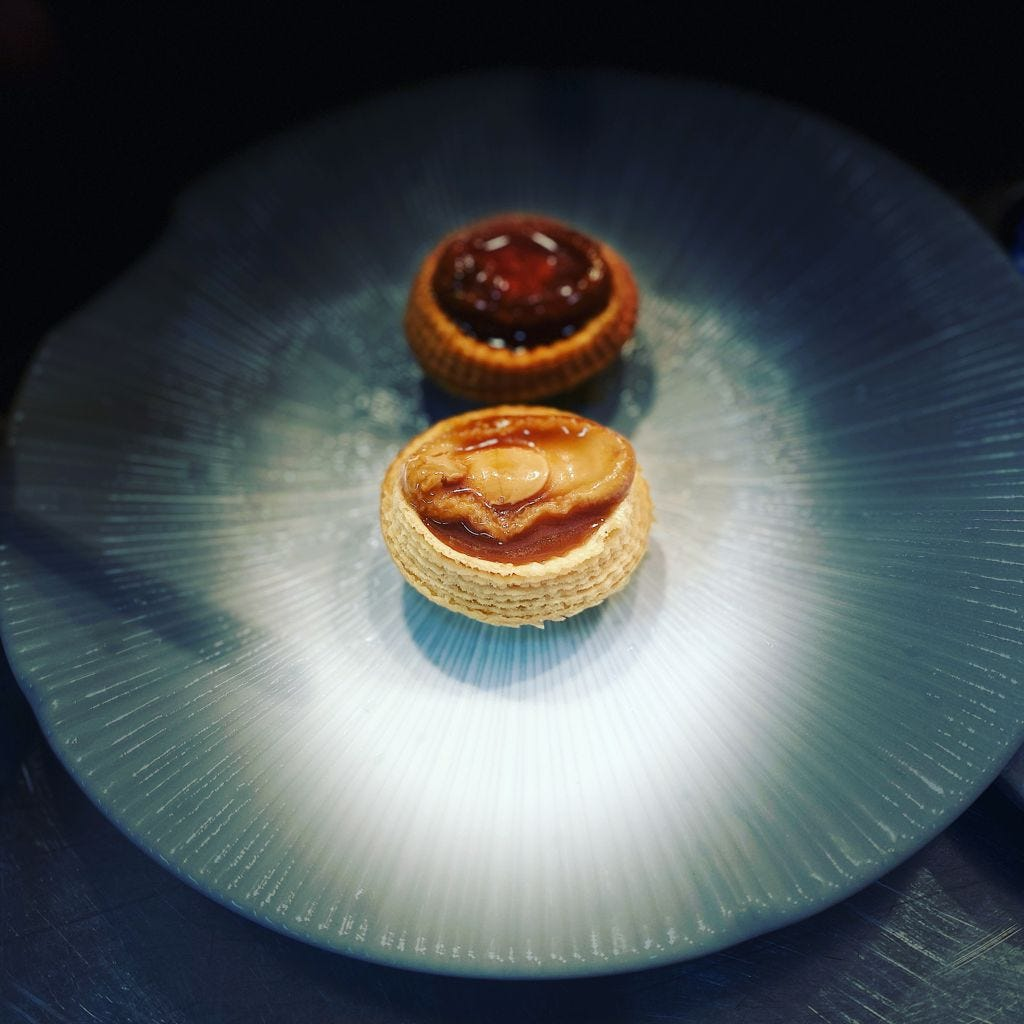 A sideview of a cooked abalone encase in a pastry tart case in the centre of a textured dinner plate
