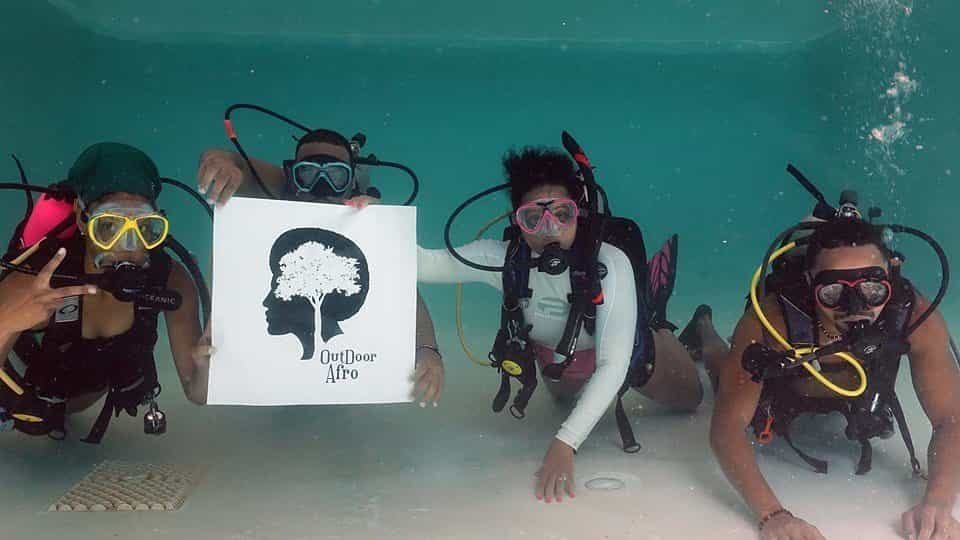 four scuba divers hold an outdoor afro sign