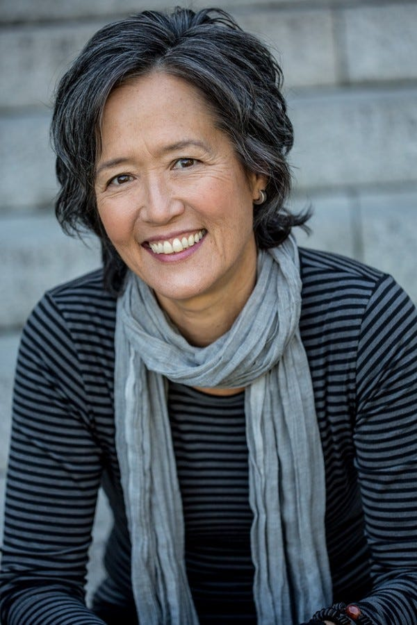 Portrait shot of author Ruth Ozeki wearing a grey scarf and black and grey striped shirt, smiling at the camera