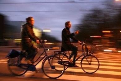 May be an image of one or more people, people riding bicycles, bicycle, street and road